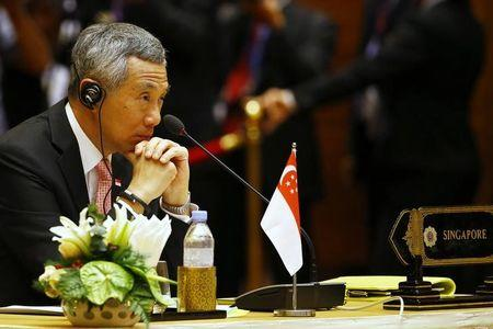 Singapore's PM Lee listens to speech during plenary session of 25th ASEAN summit at Myanmar International Convention Centre in Naypyitaw