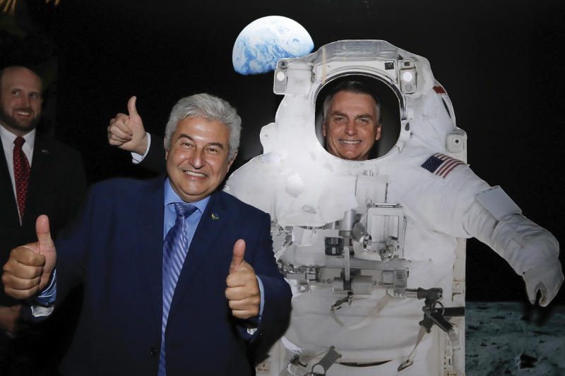 In this handout photo released by Brazil's Presidential Press Office, Brazil's President Jair Bolsonaro poses for a photo standing behind a life size cardboard cutout of a U.S. astronaut, alongside the Minister of Science and Technology Marcos Cesar Pontes, during a private event at the U.S. Embassy celebrating the July 4th Independence Day and the upcoming 50th anniversary of the Apollo 11 moonwalk, in Brasilia, Brazil. (Carolina Antunes/Brazil's Presidential Press Office via AP)