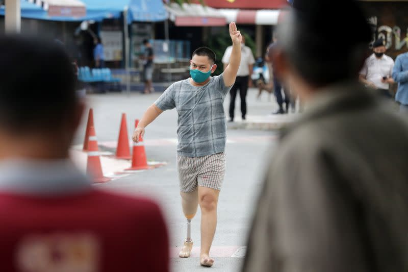 Nutchanon Pairoj flashes a three-finger salute outside a prison in Pathum Thani province
