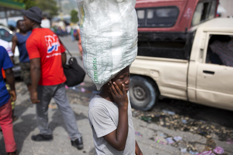 In this May 23, 2017 photo, Watson Saint Fleur balances water for sale on his head in the streets of Petion-Ville, a suburb of Port-au-Prince, Haiti. Watson is 12 but he's never attended a day of school. He's toiled in hardship doing household chores and peddling plastic bags of drinking water along city streets noisy with motorbikes and trucks. (AP Photo/Dieu Nalio Chery)