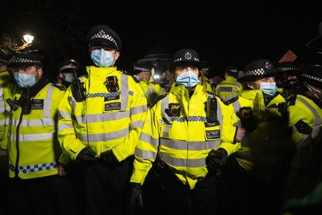 Police officers form a line as people gather in Clapham Common