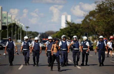 Riot-police are seen in line behind an university student during a protest against cuts to federal spending on higher education planned by Brazil's President Jair Bolsonaro's right-wing government in Brasilia, Brazil May 15, 2019. REUTERS/Adriano Machado