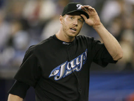 FILE PHOTO - Toronto Blue Jays starting pitcher Roy Halladay adjusts his cap while walking off the field against the Chicago White Sox during the fourth inning of their MLB American League baseball game in Toronto, May 4, 2008. REUTERS/ Mike Cassese