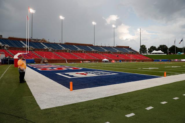 A security guard stands on the field during an inclement weather delay before an NCAA college football game between TCU and SMU, Friday, Sept. 7, 2018, in Dallas. (AP Photo/Jim Cowsert)