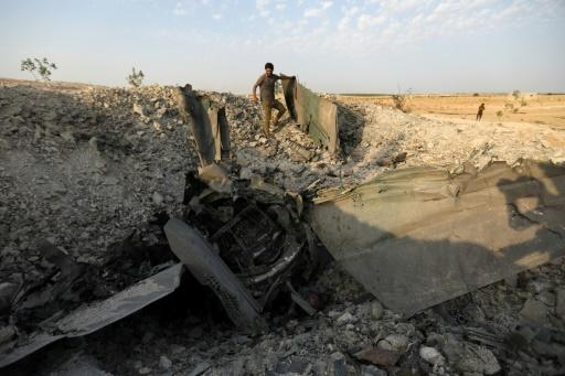 A rebel fighter stands near the remains of a downed regime warplane near the jihadist-held town of Khan Sheikhun in the south of Idlib province on Wednesday