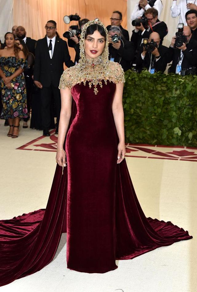 <p>Chopra paired a strapless Ralph Lauren dress with a jeweled hood. (Photo: Getty Images) </p>