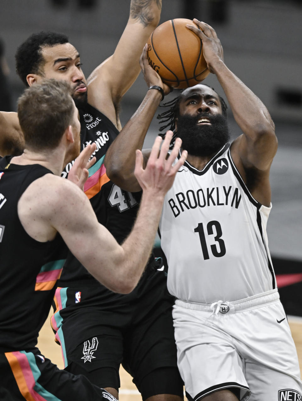 Brooklyn Nets' James Harden (13) attempts to shoot as he is defended by San Antonio Spurs' Trey Lyles (41) and Jakob Poeltl during the second half of an NBA basketball game, Monday, March 1, 2021, in San Antonio. (AP Photo/Darren Abate)