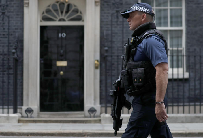 An armed police officer walks past the entrance of 10 Downing Street in London, Wednesday, Aug. 28, 2019. Prime Minister Johnson has written to fellow lawmakers explaining his decision to ask Queen Elizabeth II to suspend Parliament as part of the government plans before the Brexit split from Europe. (AP Photo/Frank Augstein)