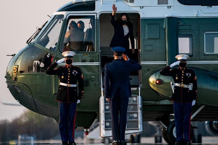 Vice President Kamala Harris waves from a helicopter with Marines standing at salute