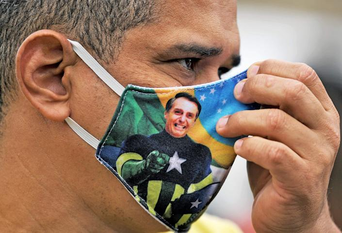 A Bolsonaro supporter wears a face mask with the president's image during a demonstration in Rio de Janeiro: AFP via Getty Images