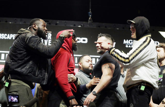 Deontay Wilder, left, and Tyson Fury face off for photographers during a news conference for their upcoming WBC heavyweight championship boxing match, Wednesday, Feb. 19, 2020, in Las Vegas. (AP Photo/Isaac Brekken)
