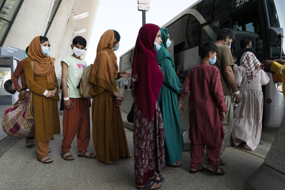Families evacuated from Kabul, Afghanistan, wait to board a bus after they arrived at Washington Dulles International Airport, in Chantilly, Va., on Friday, Aug. 27, 2021. (AP Photo/Jose Luis Magana)