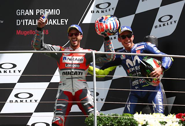 Motorcycling - MotoGP - Italian Grand Prix - Mugello Circuit, Scarperia, Italy - June 3, 2018 Runner up Ducati's Andrea Dovizioso (L) celebrates on the podium alongside third place Movistar Yamaha MotoGP's Valentino Rossi (R) REUTERS/Alessandro Bianchi