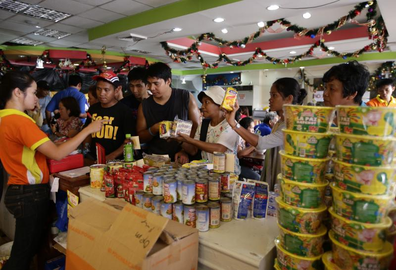 FILE - In this Nov. 25, 2013 file photo, typhoon survivors shop for groceries as a sense of normalcy returns in Typhoon Haiyan-hit Tacloban city, central Philippines. Monday, Nov. 25, 2013. The Philippine economy expanded 7.2 percent in 2013 despite the havoc wrought in the last months of the year by the super typhoon, an earthquake and a weeks-long gun battle that shut down a major port city. Even then, the Philippines was the second best performing economy in Asia after China in the fourth quarter, officials said. (AP Photo/Bullit Marquez, File)