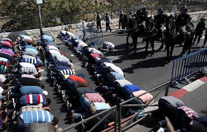 Israeli police stand guard as Palestinian Muslims pray on the streets of east Jerusalem following restrictions by Israeli police preventing Palestinians under 40 years old from entering the Al-Aqsa mosque compounds, on October 16, 2015 (AFP Photo/Thomas Coex)