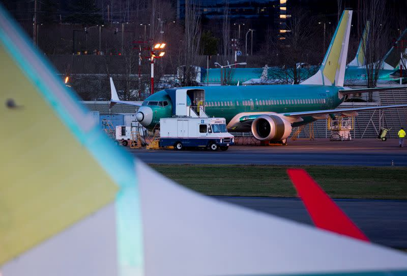 A service truck is seen stopped next to a Boeing 737 Max aircraft in storage at the Renton Municipal Airport in Renton