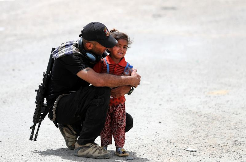 An Iraqi soldier helps a girl whose family has fled their home in the west of Mosul on May 26, 2017 (AFP Photo/KARIM SAHIB)