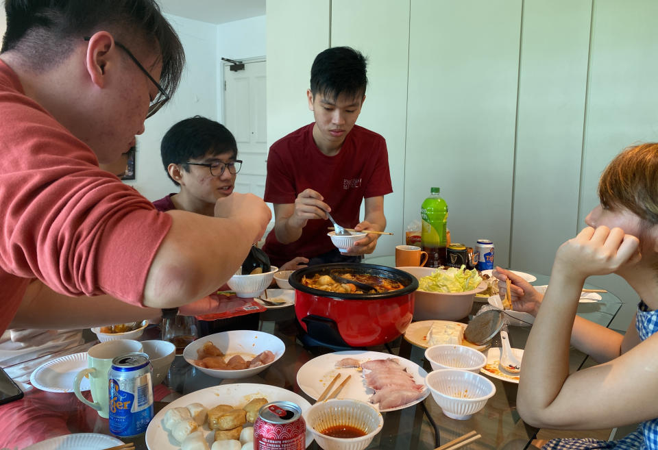 Malaysian students, from left, Felix Mong, Ter Leong Kern and Siew Ee Sung enjoy a Lunar New Year hot pot lunch provided by their Malaysian host Chan Jit Yen, right, at her rented apartment in Singapore, Saturday, Feb. 13, 2021. With Malaysian workers and students stranded in the city state over the Lunar New Year due to coronavirus travel restrictions, the Malaysian Association in Singapore has called on Malaysians to treat students to a meal. (AP Photo/Annabelle Liang)