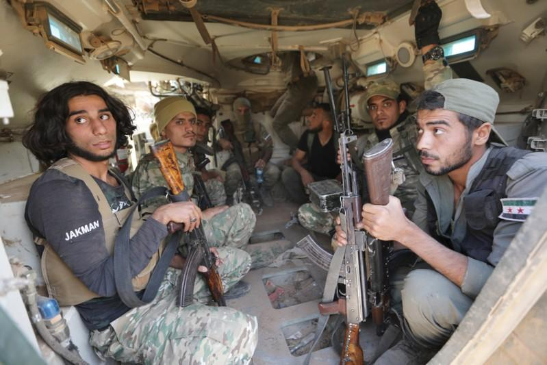 Turkey-backed Syrian rebel fighters ride in their military tank near the border town of Tal Abyad