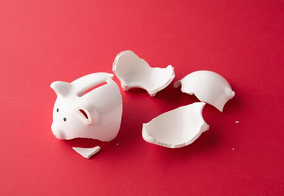 Broken whiter ceramic piggy bank in pieces on red surface
