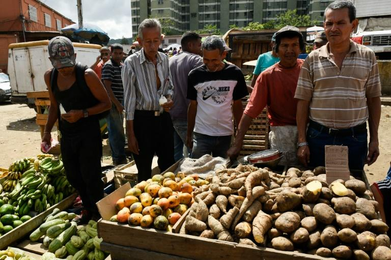 People buy groceries at the municipal market of Coche, a neighborhood in Caracas