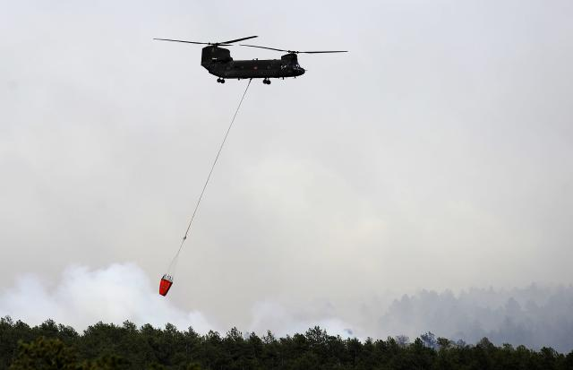 COLORADO SPRINGS, CO - JUNE 12: A helicopter prepares to make a water drop while fighting the Black Forest Fire on June 12, 2013 north of Colorado Springs, Colorado. The fire has reportedly burned 80 to 100 homes and has charred at least 8,000 acres. (Photo by Chris Schneider/Getty Images)