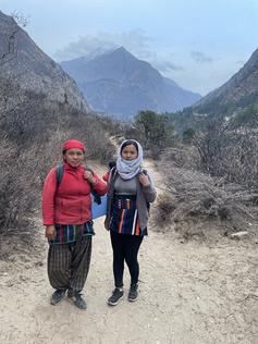 Two women pictured outside in front of mountains.
