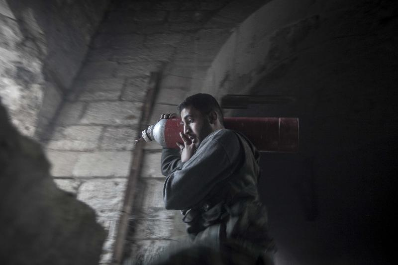 In this Saturday, Nov. 03, 2012 photo, a rebel fighter carries an improvised explosive device as they try to repel a coordinated attack using mortar, tank and aerial artillery fire carried out by loyalists to President Bashar Assad in the Jedida district of Aleppo, Syria. (AP Photo/Narciso Contreras)