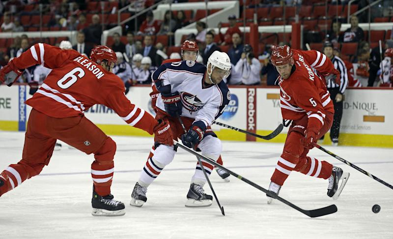 Carolina Hurricanes' Tim Gleason (6) and Mike Komisarek (5) defend against Columbus Blue Jackets' Marian Gaborik, of Slovakia, during the first period of a preseason NHL hockey game in Raleigh, N.C., Wednesday, Sept. 18, 2013. (AP Photo/Gerry Broome)