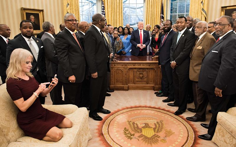 Kellyanne Conway (L) checks her phone after taking a photo as Donald Trump and leaders of historically black universities and colleges pose for a group photo in the Oval Office - AFP or licensors