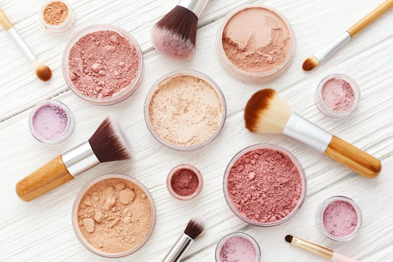 Various pots of makeup powders with makeup brushes scattered around them