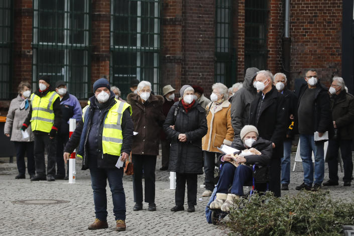 People wait for transportation as they leave the vaccination center against the COVID-19 disease in the district Treptow in Berlin, Germany, Thursday, Jan. 28, 2021. (AP Photo/Markus Schreiber)
