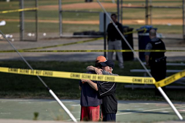 <p>Two people hug in front of police crime scene tape following a shooting during a congressional baseball practice hug near the Eugene Simpson Stadium Park in Alexandria, Va., on Wednesday, June 14, 2017. (Photo: Andrew Harrer/Bloomberg via Getty Images) </p>