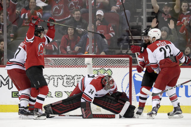 New Jersey Devils center Nico Hischier, second from left, of Switzerland, and left wing Marcus Johansson, back right, of Sweden, react after Johansson scored a goal on Carolina Hurricanes goaltender Petr Mrazek (34), of the Czech Republic, during the first period of an NHL hockey game, Sunday, Feb. 10, 2019, in Newark, N.J. (AP Photo/Julio Cortez)