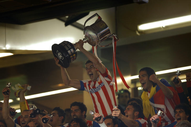 Atletico de Madrid's Gabi lift the trophy after defeating Real Madrid in the Copa del Rey final soccer match at the Santiago Bernabeu stadium in Madrid, Spain, Friday, May 17, 2013. (AP Photo/Daniel Ochoa de Olza)