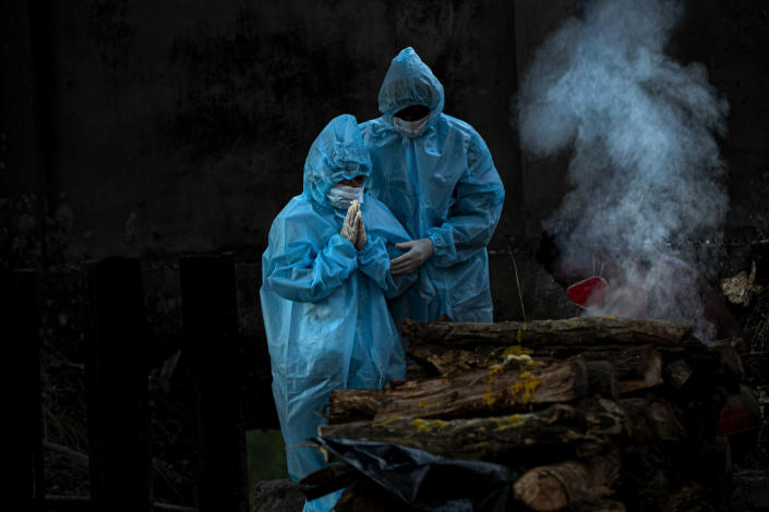 A 9-year-old boy, left, wearing personal protective equipment performs rituals during the cremation of his father who died of COVID-19 in Gauhati, India, Monday, Sept. 28, 2020. (AP Photo/Anupam Nath)