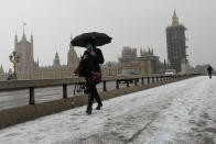 A woman walks over Westminster Bridge as temperatures dropped below freezing during the third coronavirus lockdown in London, Tuesday, Feb. 9, 2021. (AP Photo/Kirsty Wigglesworth)