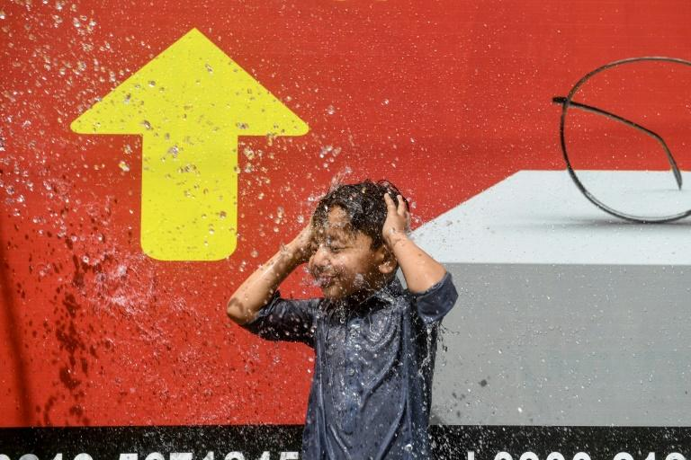 A boy enjoys a shower on a street in the southern port city of Karachi (AFP Photo/Asif HASSAN)