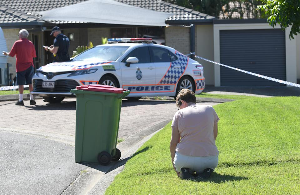 Local resident Louise Christy is seen kneeling in mourning outside the home of murder victim Kelly Wilkinson on the Gold Coast. Source: AAP