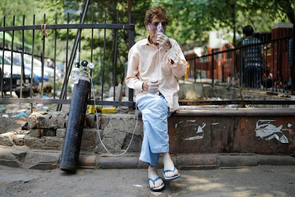 A patient, wearing an oxygen mask, sits outside Lok Nayak Jai Prakash Narayan Hospital (LNJP) in New Delhi, 22 April