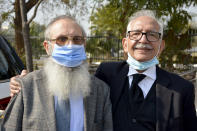 Mehmood A. Sheikh, right, defense lawyer, and Ahmed Saeed Sheikh, father of British-born Pakistani Ahmed Omar Saeed Sheikh, arrive at the Supreme Court for an appeal hearing in the Daniel Pearl case, in Islamabad, Pakistan, Thursday, Jan. 28, 2021. THe court on Thursday has ordered the release of Sheikh convicted and later acquitted in the gruesome beheading of American journalist Daniel Pearl in 2002. The court also dismissed an appeal of Sheikh's acquittal by Pearl's family. (AP Photo/Waseem Khan)
