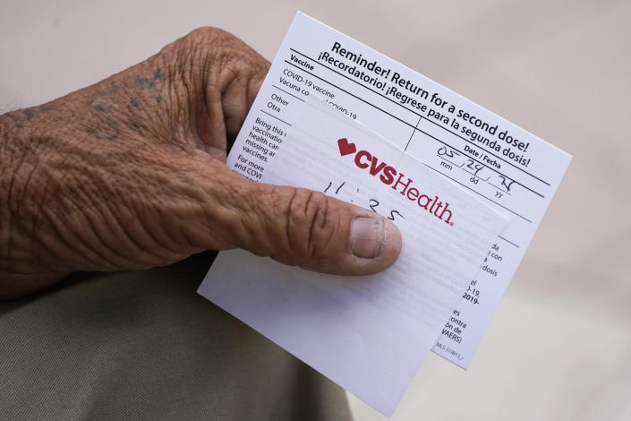 FILE - In this May 3, 2021 file photo, a man holds his vaccination reminder card after having received his first shot at a pop-up vaccination site in the Little Havana neighborhood of Miami. Billions more in profits are at stake for some vaccine makers as the U.S. moves toward dispensing COVID-19 booster shots to shore up Americans' protection against the virus. Drugstore chains CVS Health and Walgreens could bring in more than $800 million each in revenue, according to Jeff Jonas, a portfolio manager with Gabelli Funds. (AP Photo/Wilfredo Lee)
