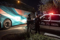 Mexican police and National Guard stand near a parked bus near the Rio Grande river in Ciudad Acuna, Mexico, at dawn Thursday, Sept. 23, 2021, on the border with Del Rio, Texas. Mexico has been ramping up efforts to relieve migrant numbers at this segment of the border. (AP Photo/Felix Marquez)