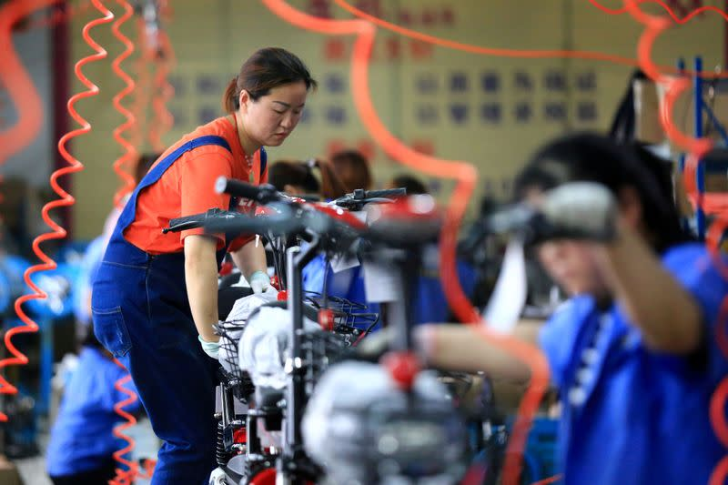 FILE PHOTO: Woman work on manufacturing electric bicycles at a factory in Huaian, Jiangsu