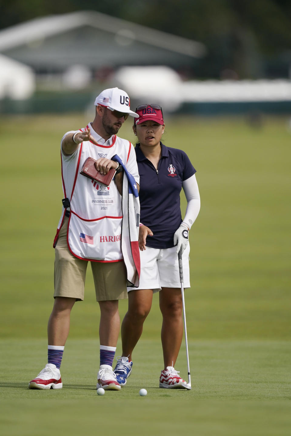 United States' Mina Harigae talks to her caddie on the 14th green during practice for the Solheim Cup golf tournament, Friday, Sept. 3, 2021, in Toledo, Ohio. (AP Photo/Carlos Osorio)