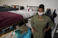 "Cidney Oliver poses for a photo, Wednesday, April 7, 2021, by the bunk she sleeps on at a YWCA shelter for women lacking housing in Seattle. Earlier in the day, Oliver received the first dose of the Moderna COVID-19 vaccine at a clinic staffed by workers from Harborview Medical Center at the shelter. ""It was important for me to protect myself and the health and welfare of others,"" Oliver said. (AP Photo/Ted S. Warren)"