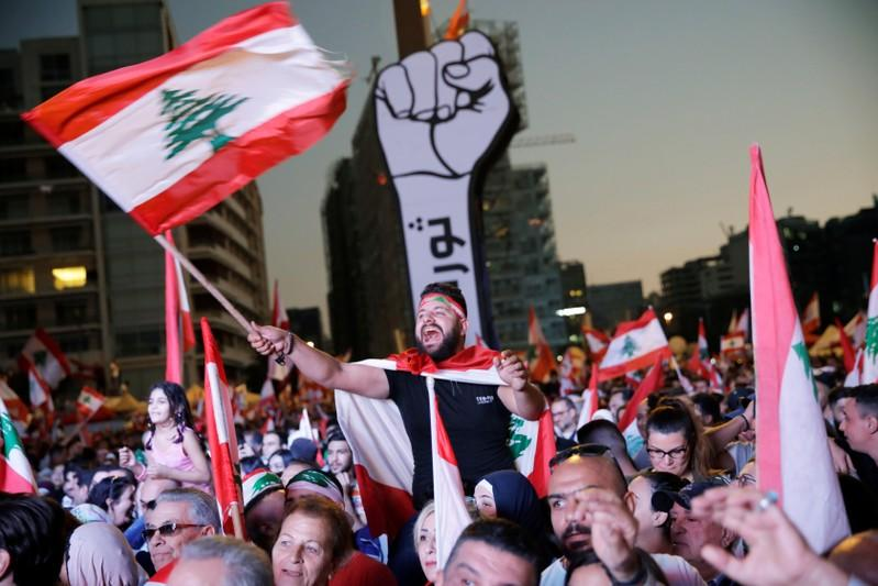 A demonstrator waves a national flag as protesters gather at Martyrs' Square during ongoing anti-government protests in downtown Beirut