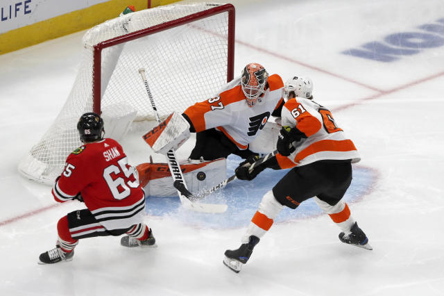 Philadelphia Flyers goaltender Brian Elliott makes a pad save on a shot by Chicago Blackhawks center Andrew Shaw (65) as Justin Braun also defends during the first period of an NHL hockey game Thursday, Oct. 24, 2019, in Chicago. (AP Photo/Charles Rex Arbogast)