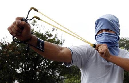 A demonstrator uses a slingshot against the National Guard during a protest against Venezuelan President Nicolas Maduro's government in San Cristobal, about 410 miles (660 km) southwest of Caracas, February 27, 2014. REUTERS/Carlos Garcia Rawlins