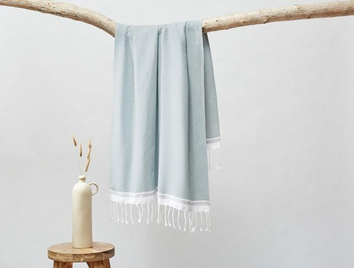 """Another one of our favorite housewarming gifts is a set of fresh <a href=""""https://www.architecturaldigest.com/gallery/best-bath-towels?mbid=synd_yahoo_rss"""" rel=""""nofollow noopener"""" target=""""_blank"""" data-ylk=""""slk:bath towels"""" class=""""link rapid-noclick-resp"""">bath towels</a>. We love this pick from Coyuchi: an organic, lightweight towel that absorbs water quickly and has plenty of style. It's available in white, pewter, shadow, lake, and sea spray (pictured). $58, Coyuchi. <a href=""""https://www.coyuchi.com/organic-cotton-mediterranean-towels.html"""" rel=""""nofollow noopener"""" target=""""_blank"""" data-ylk=""""slk:Get it now!"""" class=""""link rapid-noclick-resp"""">Get it now!</a>"""